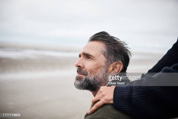 woman's hand on man's shoulder by the sea - contemplation stock pictures, royalty-free photos & images