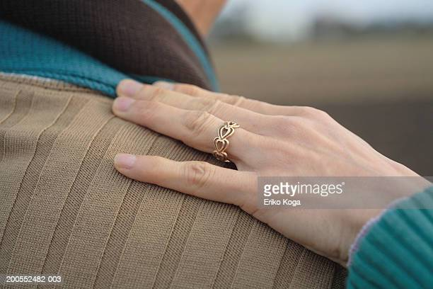 Woman's hand on man's shoulder, close-up, rear view