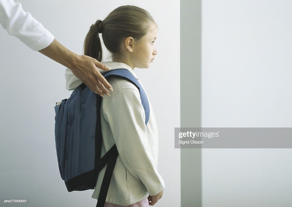 Woman's hand on shoulder of girl with backpack : Stock Photo