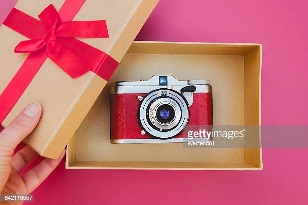 Womans hand opening a gift box with a beautiful analog camera inside