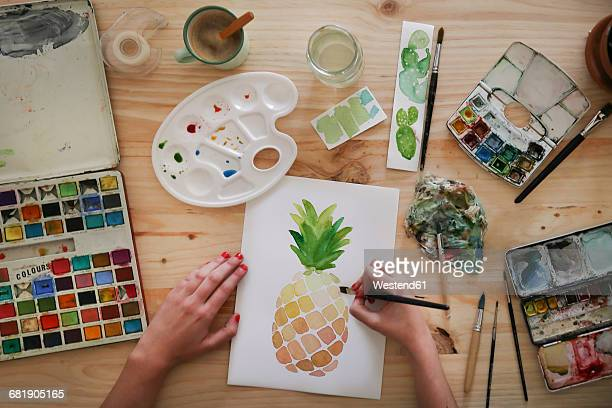 Womans hand painting aquarelle of a pineapple on desk in her studio