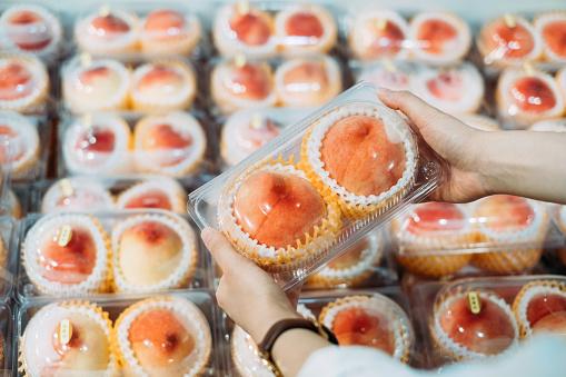 Woman's hand picking fresh white peaches at supermarket - gettyimageskorea