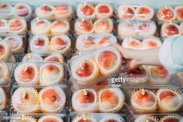woman's hand picking fresh white peaches at supermarket - fülle stock-fotos und bilder