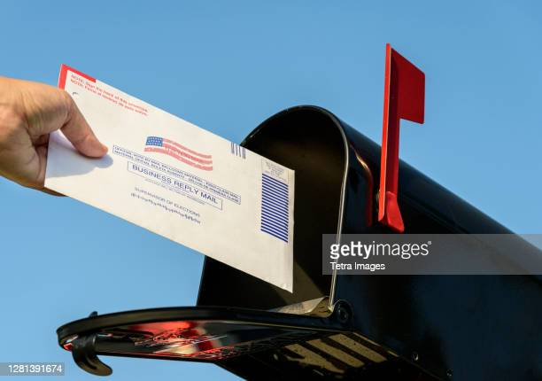 woman's hand placing a 2020 mail-in election ballot in a rural mailbox - voting by mail stock pictures, royalty-free photos & images