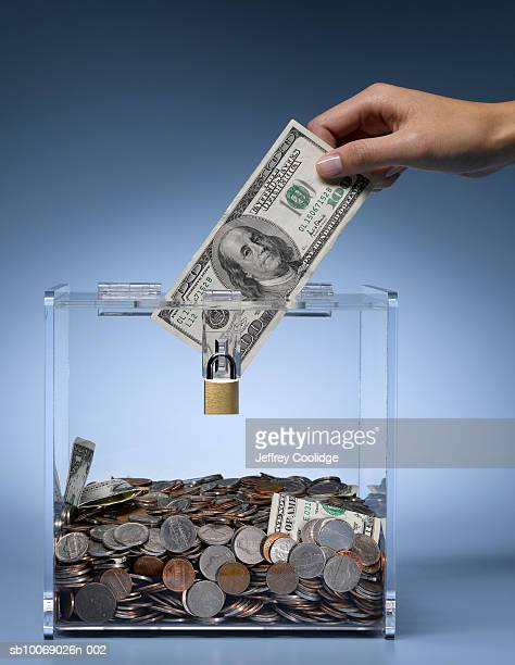 Woman's hand placing dollar bill into collection box filled with money, studio shot