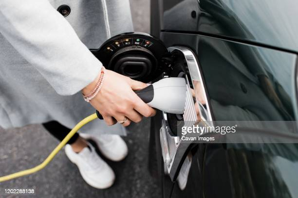 woman's hand plugging in a charging lead to her electric car - electric car stock pictures, royalty-free photos & images