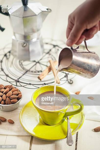 Womans hand pouring almond milk into cup of coffee