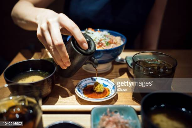 woman's hand pouring soy sauce over plate and ready to enjoy the fresh japanese seafood rice bowl in restaurant - soy sauce stock pictures, royalty-free photos & images