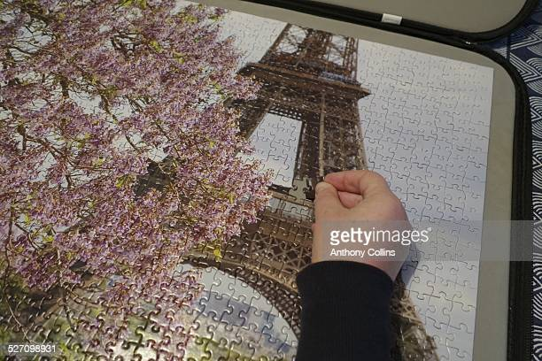 Woman's hand putting final piece into a jigsaw puzzle of the Eiffel Tower in Spring with cherry blossom
