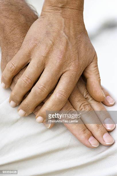 Woman's hand resting on top of man's hand, close-up