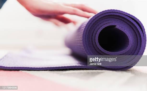 woman's hand rolling yoga mat - fitnessmat stockfoto's en -beelden