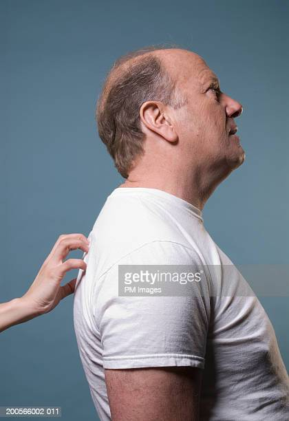 Woman's hand scratching middle aged man's back, side view