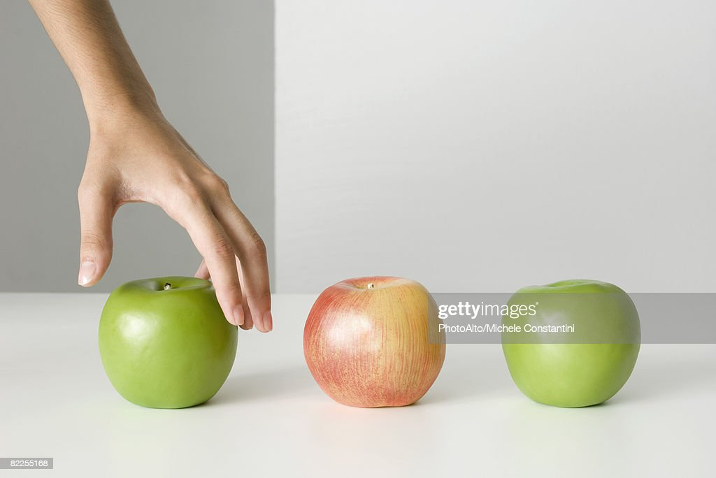 Woman's hand selecting apple : Stock Photo