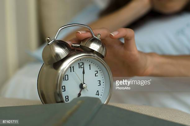 Woman's hand silencing alarm clock