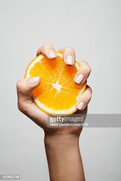 Woman's hand squeezing an orange