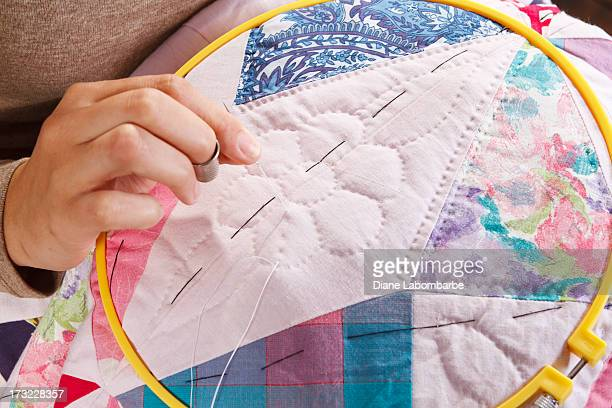 Woman's Hand Stitching A Patchwork Quilt