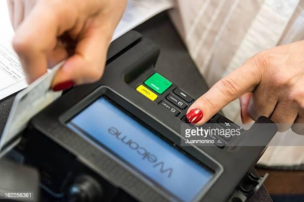 Woman's hand swipes credit card through c/c reader