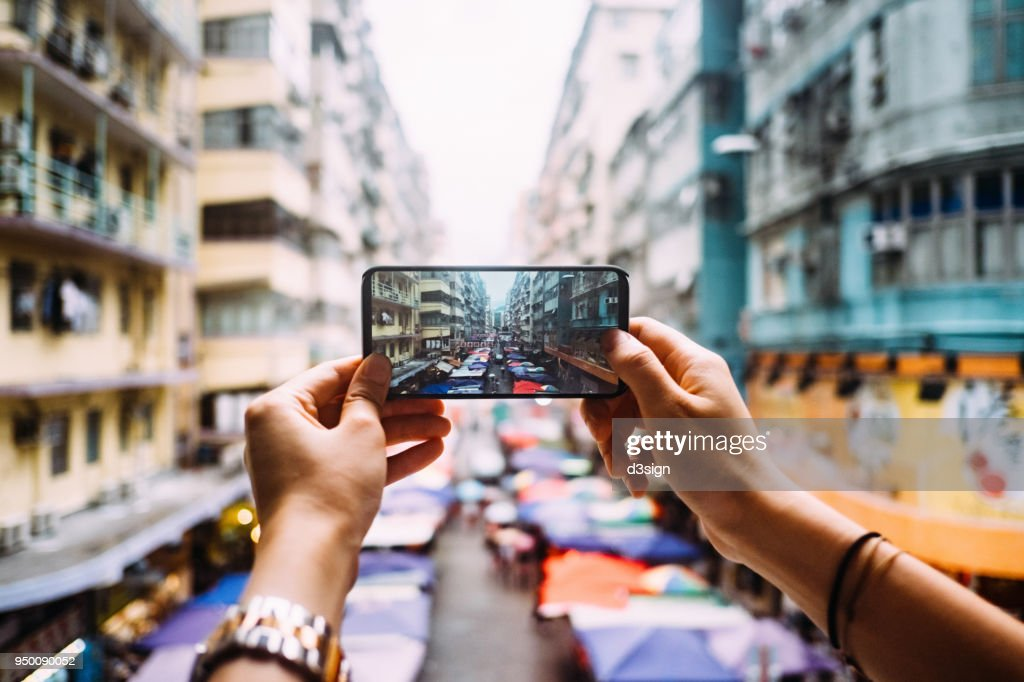 Woman's hand taking a photo of local city street view in Hong Kong with smartphone : Stock Photo