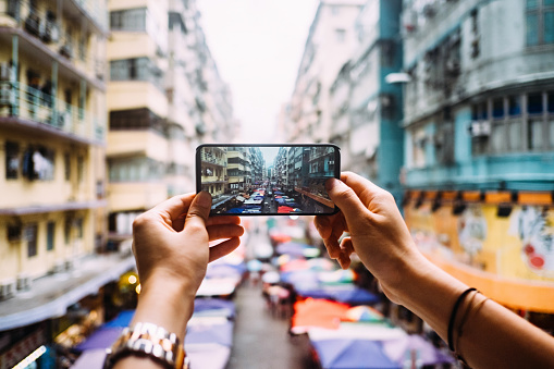 Woman's hand taking a photo of local city street view in Hong Kong with smartphone - gettyimageskorea