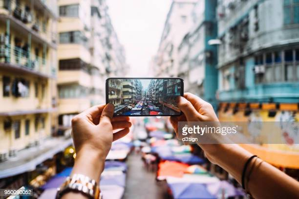 Woman's hand taking a photo of local city street view in Hong Kong with smartphone