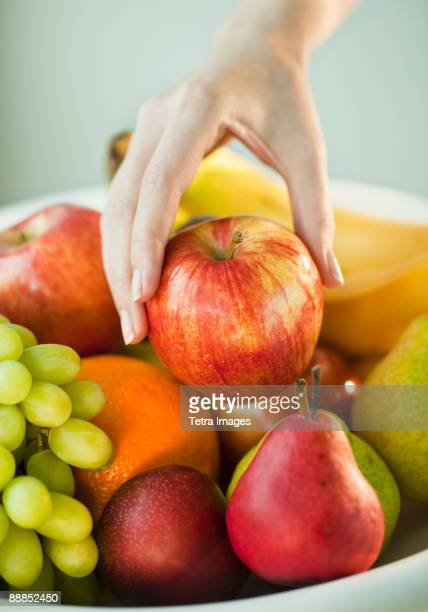 womans hand taking apple from fruit bowl - mid adult women stock pictures, royalty-free photos & images