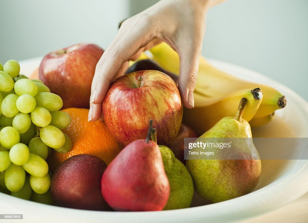 Womans hand taking apple from fruit bowl : Stock Photo