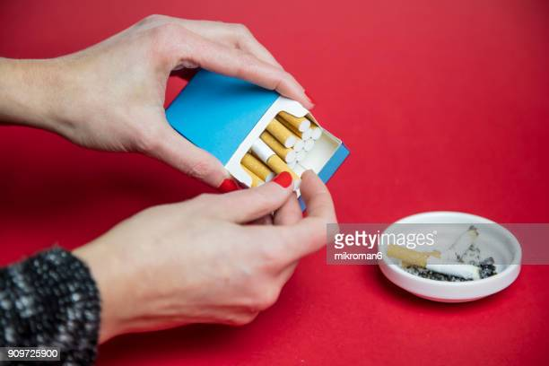 Woman's Hand taking cigarette from pack