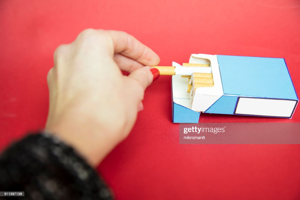 Woman's Hand taking cigarette from pack : Stock Photo