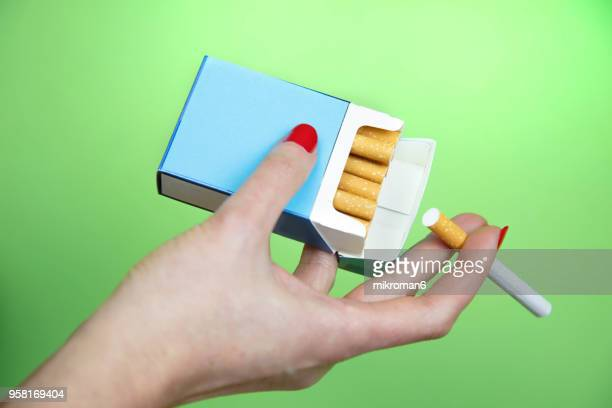 woman's hand taking cigarette from pack - cigarette packet stock pictures, royalty-free photos & images