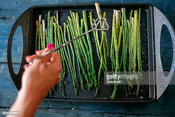 Womans hand taking grilled asparagus with tongs
