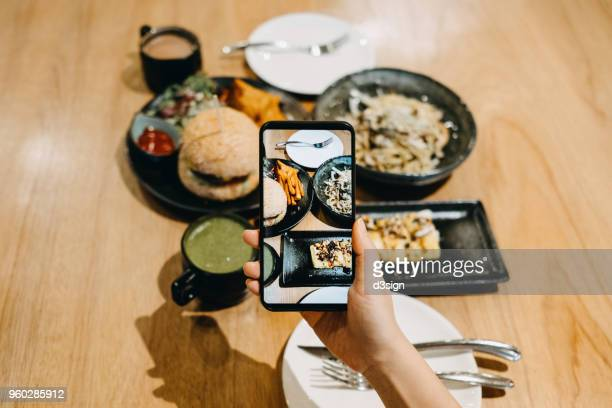 Woman's hand taking photo of food on table with mobile phone while having meal in cafe
