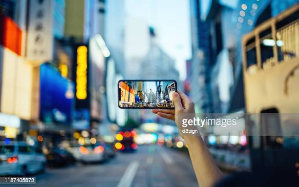 woman's hand taking photo with smartphone in busy downtown district against urban skyscrapers with multi-coloured neon signs and city traffic - photo messaging stock pictures, royalty-free photos & images