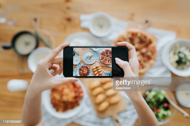 woman's hand taking pictures of food on the table with smartphone during party with friends - blogging stock pictures, royalty-free photos & images