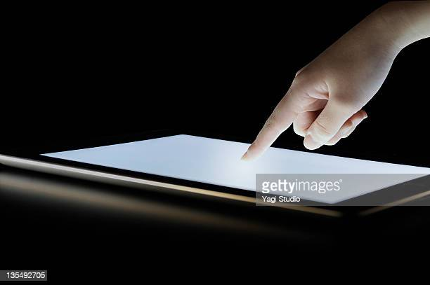 Woman's hand to touch the tablet computer