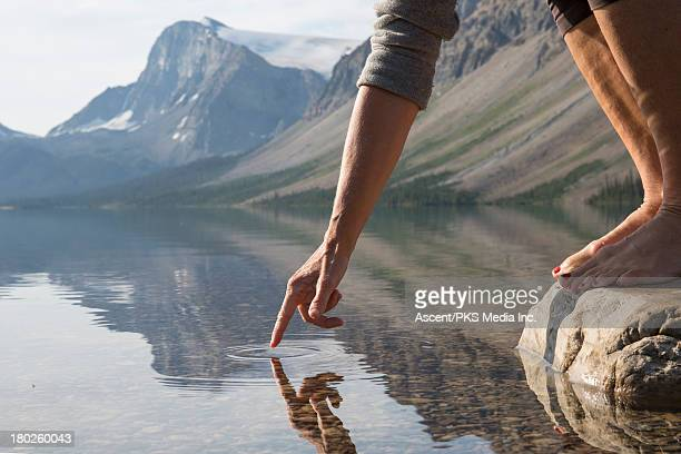 Woman's hand touches water surface, mtn lake