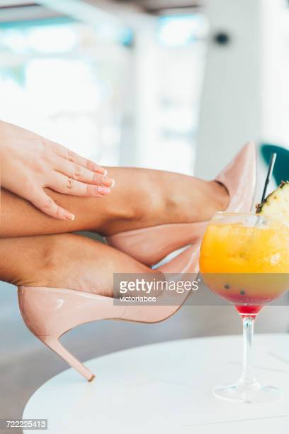 Woman's hand touching her ankles on a table with a cocktail