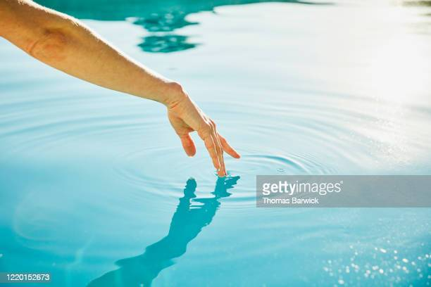 womans hand touching surface of water - touching stock pictures, royalty-free photos & images