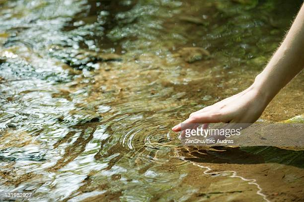 woman's hand touching water - the four elements stock pictures, royalty-free photos & images