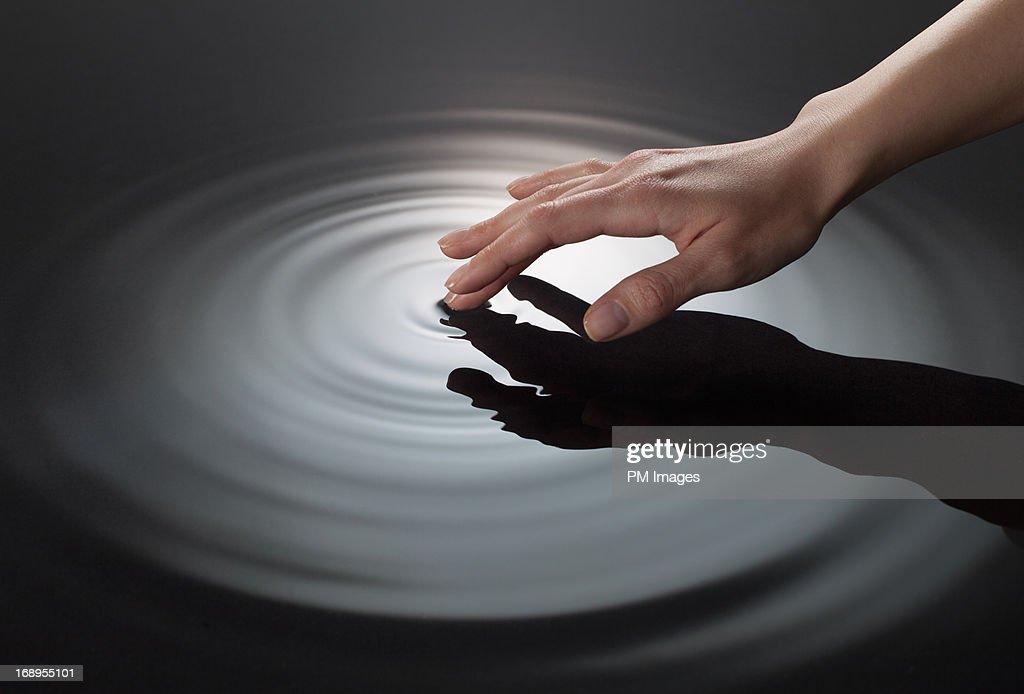 Woman's hand touching water : Stock Photo