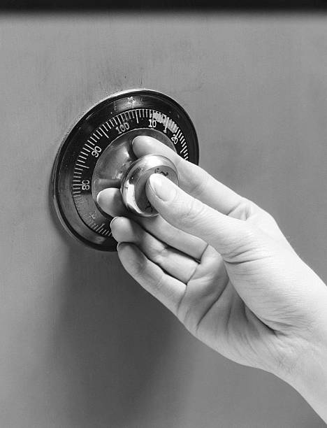 Woman's hand turning combination lock on safe door....
