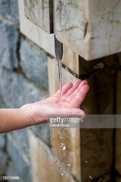 A woman's hand under a Holy water font.