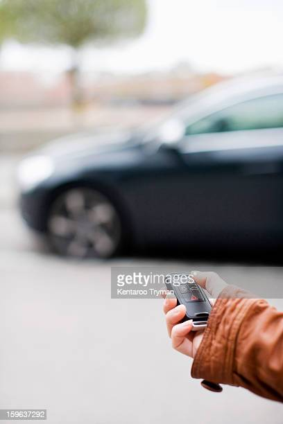 Woman's hand unlocking car with remote control