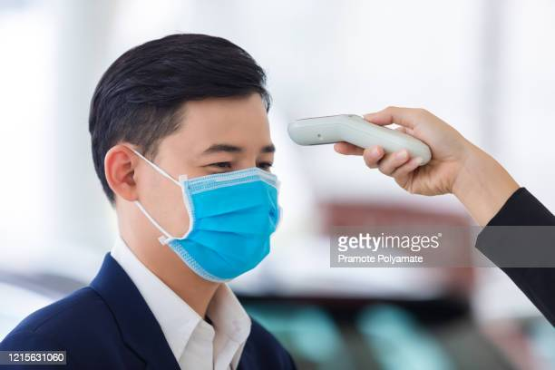 woman's hand uses an medical digital infrared thermometer, uses a a young man's body temperature monitor, the concept of a corona virus [covid-19] screening. - digital thermometer ストックフォトと画像