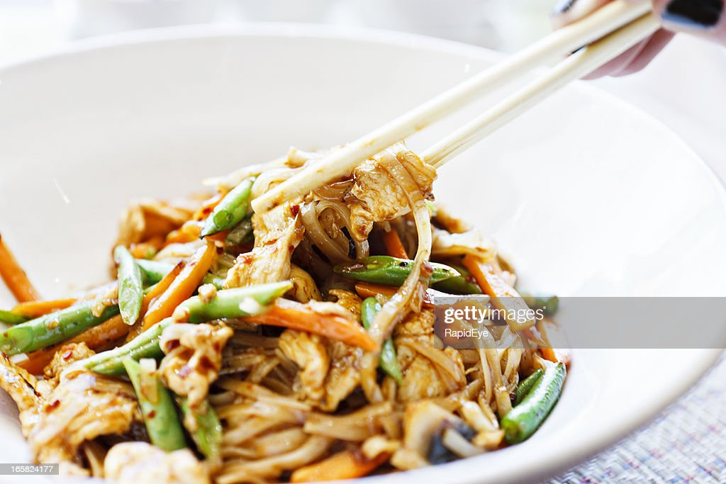 Woman's hand uses chopsticks to serve Thai chicken noodle dish : Stock Photo