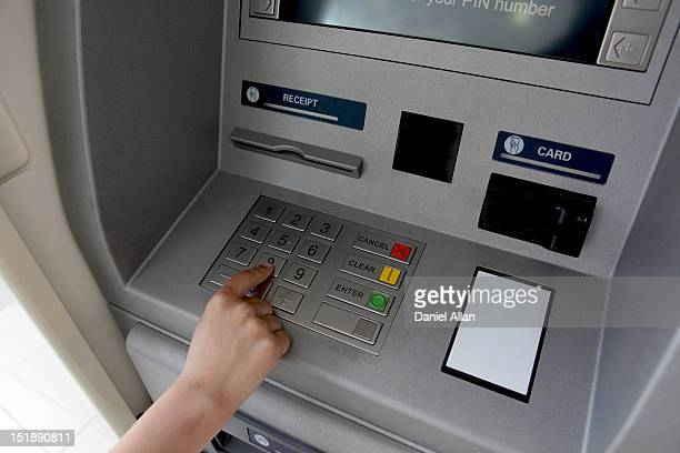 a woman's hand using a cash machine (atm) - pin stock pictures, royalty-free photos & images