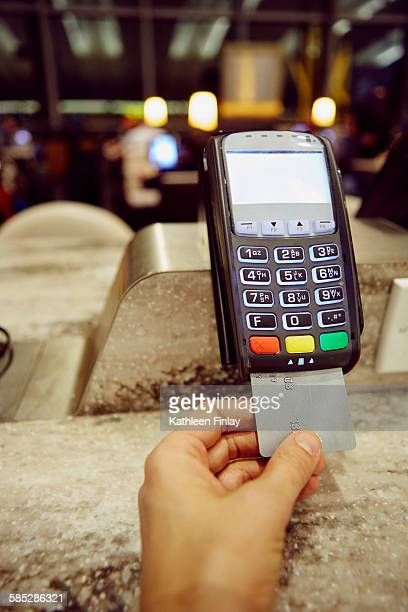 Womans hand using credit card machine for restaurant payment