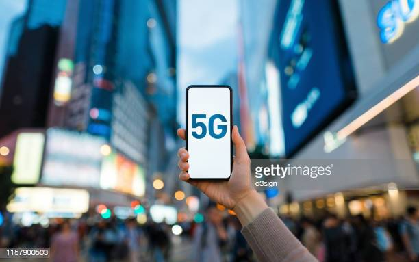 woman's hand using smartphone against illuminated financial district in the city, with the concept of 5g communications technology - 5g foto e immagini stock