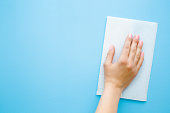 Woman's hand wiping pastel blue desk with white paper napkin. General or regular cleanup. Close up. Empty place for text or logo. Top view.