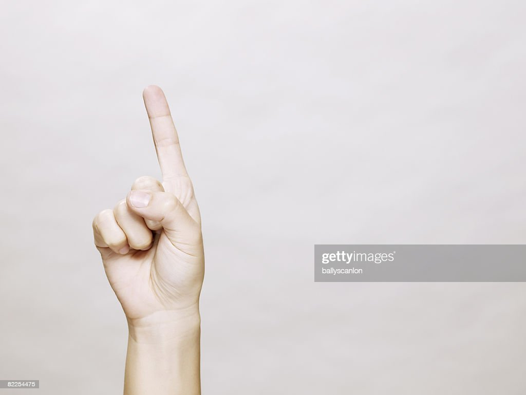 Woman's hand with finger pointing up : Stock Photo