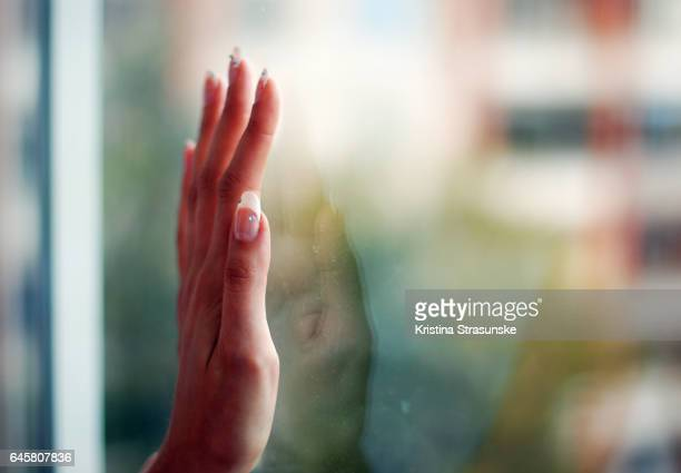 woman's hand with manicured nails reflected in a window